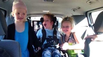 Three siblings in an accessible vehicle. Two girls either side of a young boy in a wheelchair
