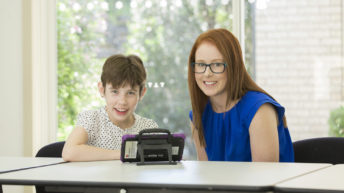 A young girl and a therapist sitting at a table using a communication device