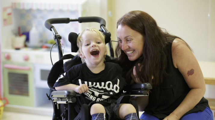 Young boy with cerebral palsy in a wheelchair laughing at something in the distance while his mother looks at him and is laughing too.