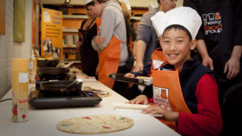 A young boy wearing a white chef hat and an orange apron over his clothes smiling at the camera as he sits at a table with cooking instruments