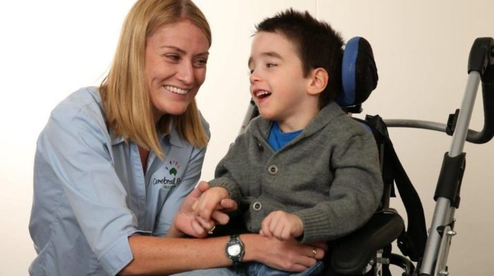 A Cerebral Palsy Alliance therapist with a child who is in a wheelchair.