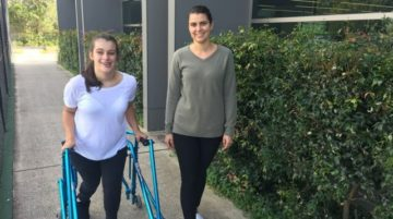 Two women walking - the woman on the left is a teen with cerebral palsy using a walker, she is wearing work out clothes and her hair is in a pony tail. On the right is a woman who is wearing a long sleeve top and black pants. They are walking on a path past a green hedge.