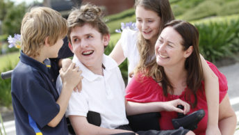 teenage boy in a wheelchair surrounded by his brother,sister and mother