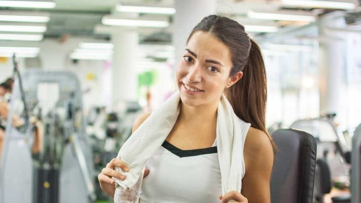 Woman in gym with towel