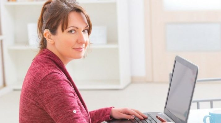Middle aged woman wearing a red cardigan, hair in a pony tail and with a hearing aid, looking at the camera. She has a laptop in front of her. She is sitting at a table in what looks like a kitchen.
