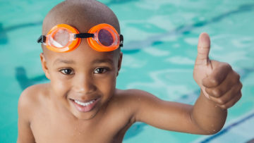 Boy thumbs up at side of pool