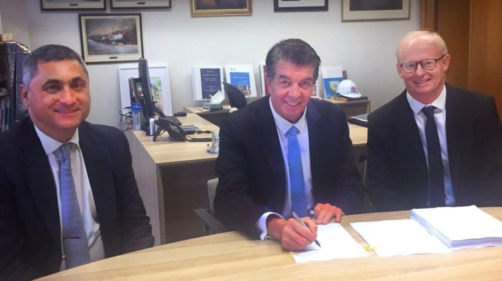 Cerebral Palsy Alliance chairman Paul Masi, the honourable Ray Williams, MP Minister for Multiculturalism, and Minister for Disability Services, with Cerebral Palsy Alliance CEO Rob White, at a desk signing paperwork.