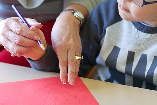 Volunteer helping child to draw a hand